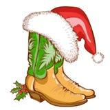 Botas de vaquero de la Navidad y sombrero de Papá Noel Imagenes de archivo
