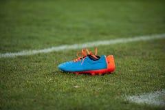 Botas del fútbol en campo Imagen de archivo