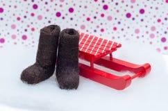 Botas diminutas de feltro do marrom e trenó vermelho Imagem de Stock Royalty Free