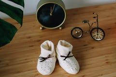 Botas e brinquedos do ` s do bebê no fundo de madeira Bebê de espera sapatas brancas para recém-nascido na tabela imagens de stock royalty free
