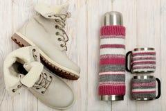 Botas ligeras del invierno y un termo en la cubierta hecha punto en el bri Imagen de archivo