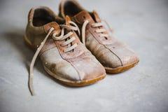 Botas marrones viejas del grunge en fondo gris del cemento Fotos de archivo libres de regalías