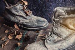 Botas militares en el de madera Imagenes de archivo