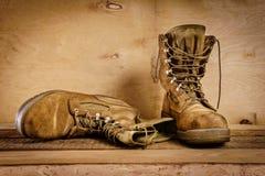 Botas militares viejas en la tabla Foto de archivo