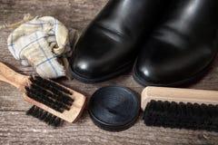 Botas negras con el cepillo de madera para limpiar Imágenes de archivo libres de regalías