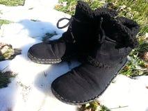 Botas negras en nieve de fusión Foto de archivo