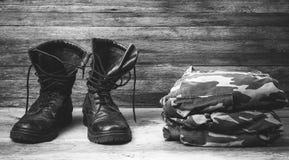 Botas para hombre negras de cuero viejas del tobillo de las botas y un uniforme militar en el primer de madera de la vista delant Imagen de archivo libre de regalías