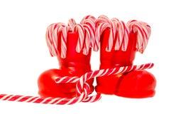 Botas rojas de Santa Claus, zapatos con las piruletas dulces coloreadas, candys Bota de San Nicolás con los regalos de los presen Foto de archivo