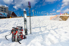Botas rojas y grises al lado del esquí que pone en nieve mullida en un esquí-re fotos de archivo