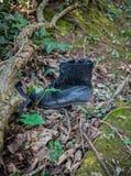 Botas sucias negras de cuero lamentables viejas dejadas en madera fotografía de archivo