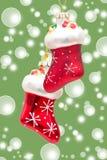 Botas vermelhas de Papai Noel sobre o fundo verde do bokeh Fotos de Stock Royalty Free