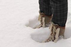 Botas vestindo da pessoa que estão na neve profunda Foto de Stock