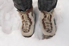 Botas vestindo da pessoa que estão na neve profunda Imagens de Stock Royalty Free
