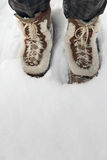 Botas vestindo da pessoa que estão na neve profunda Foto de Stock Royalty Free