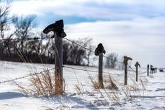 Botas viejas encima de una cerca Line en la nieve imágenes de archivo libres de regalías
