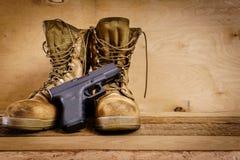 Botas y arma militares en la tabla Fotografía de archivo libre de regalías