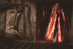 Botas y chimenea sentidas viejas con el fuego caliente en el fondo fotografía de archivo libre de regalías