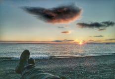 Botas y pantalones de motocicleta que miran la puesta del sol Fotos de archivo