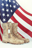 Botas y placas de identificación viejas de combate con la bandera americana Imagenes de archivo