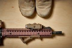 Botas y rifle militares usados en un fondo de madera Imagen de archivo