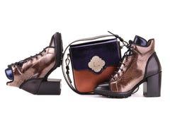 Botas y un bolso de color oro imagen de archivo