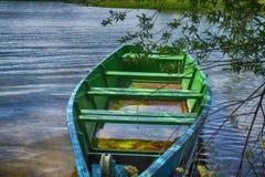 Bote azul y verde de madera por completo del agua foto de archivo