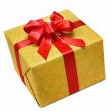 Boîte-cadeau d'or avec l'arc rouge futé Photographie stock libre de droits