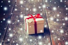 Boîte-cadeau de Brown et ruban rouge, neige avec l'étiquette sur le fond en bois Image libre de droits