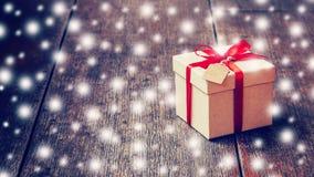Boîte-cadeau de Brown et ruban rouge, étiquette avec la neige sur le fond en bois Images libres de droits