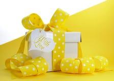 Boîte-cadeau jaune de thème avec le ruban jaune de point de polka et l'espace blanc de copie Photographie stock libre de droits