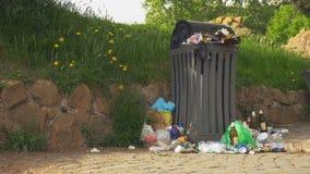 Bote de basura apretado en el parque almacen de metraje de vídeo