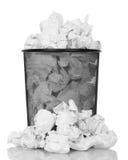 Bote de basura del metal que desborda con la basura del papel aislada en blanco Fotos de archivo