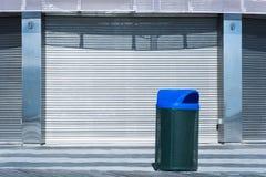 Bote de basura negro con el casquillo azul contra puerta industrial del metal Imágenes de archivo libres de regalías