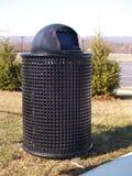 Bote de basura negro por los árboles Foto de archivo libre de regalías