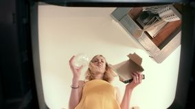 Bote de basura Point of View de una mujer joven que vacila cuando entre el papel y el plástico al reciclar almacen de metraje de vídeo