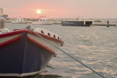 Bote de remos atracado en pequeño puerto en la puesta del sol Imagenes de archivo