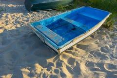 Bote de remos azul con los rayos del sol del oro de la salida del sol de la puesta del sol en la arena no ser fotografía de archivo libre de regalías