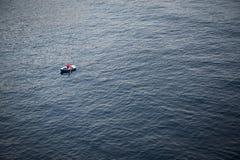 Bote de remos solo en una extensión grande del mar Imagen de archivo