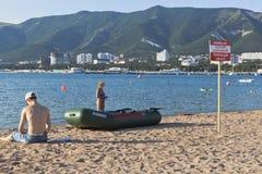 ¡Bote de salvamento y una muestra que dice el cuidado! ¡Ninguna natación! Peligro de la lesión fatal en una playa en Gelendzhik Fotos de archivo