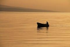 Bote pequeño con puesta del sol hermosa Imagen de archivo libre de regalías