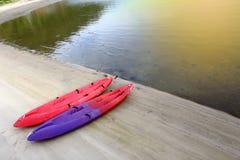Bote pequeño de la canoa de dos kajaks en rojo y púrpura en el océano de la playa de la arena imagenes de archivo