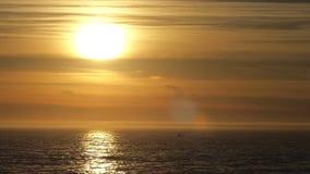Bote pequeño en el océano durante puesta del sol almacen de video