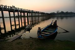 Bote pequeño en el puente de U Bein durante puesta del sol Imagenes de archivo