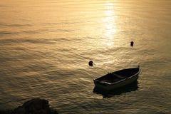 Bote pequeño en la puesta del sol Foto de archivo