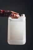 Bote plástico blanco del tanque en mano femenina imagen de archivo libre de regalías