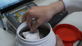 Bote plástico sin etiqueta blanco de apertura del tanque del científico químico con las sustancias químicas en la tabla del labor Fotografía de archivo libre de regalías