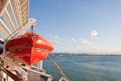 Bote salvavidas anaranjado que cuelga de la nave sobre el mar azul Fotografía de archivo libre de regalías