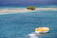 Bote salvavidas cerca de la isla desierta Foto de archivo libre de regalías