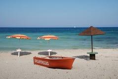Bote salvavidas y tres parasoles de playa Imagen de archivo