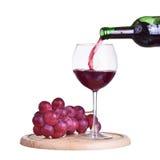 Botella aislada con el vino rojo, el vidrio y la uva en la placa de madera Foto de archivo libre de regalías